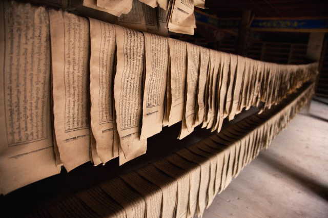 Derge Parkhang Printing House built in 1729. Rows of printed paper and printed matter hanging on a rail. Religious texts.